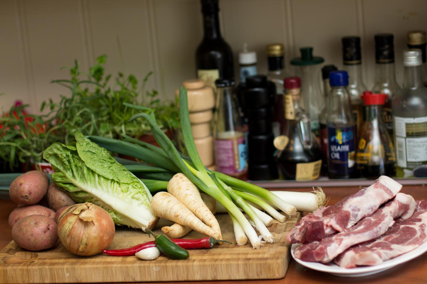 Nakkekotelett med stekte potetskiver, smørstekt purreløk, kålruletter med svin og vårløksaus med chili og jalepeno